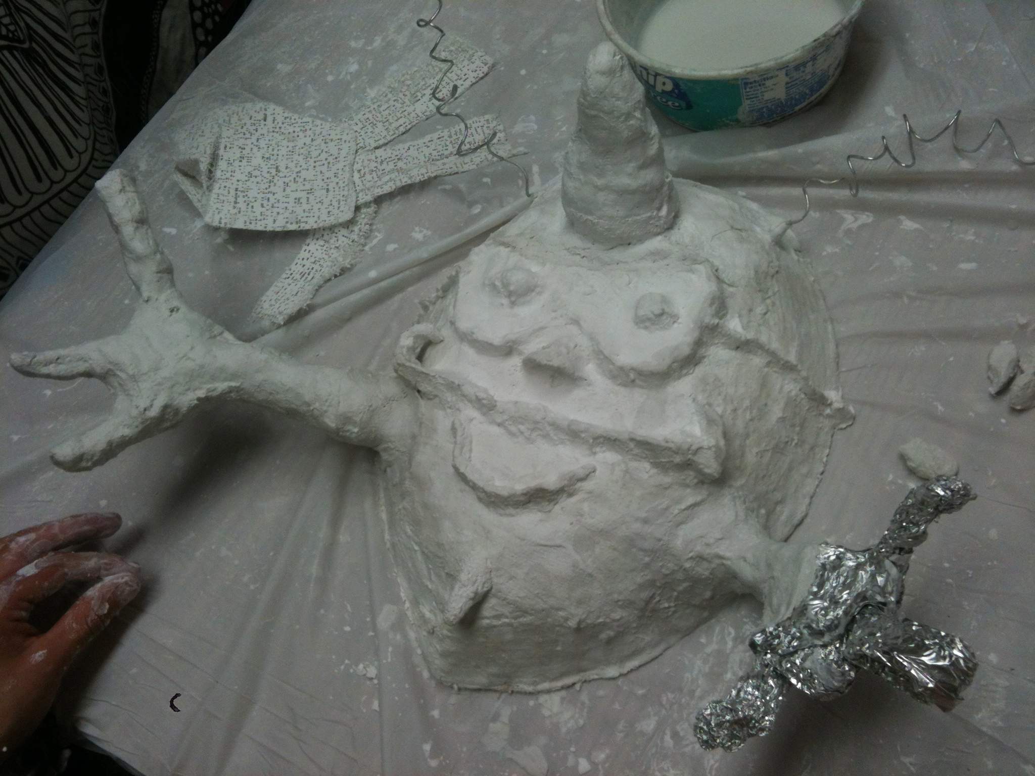 This mask uses foil as an armature. Student also added wire antennae.