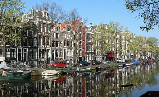 Houses in Amsterdam reflected in canal.