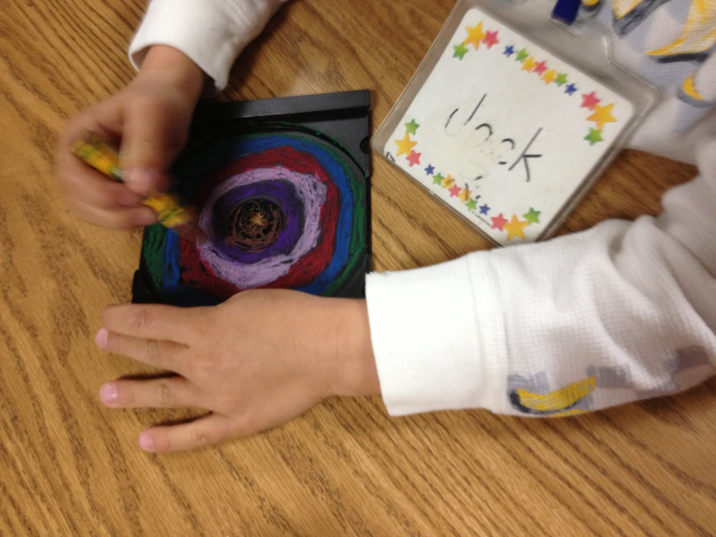 Kindergarteners use oil pastels to draw concentric circles in CD inserts. Allow one 40 minute class, plus time to assemble mural.